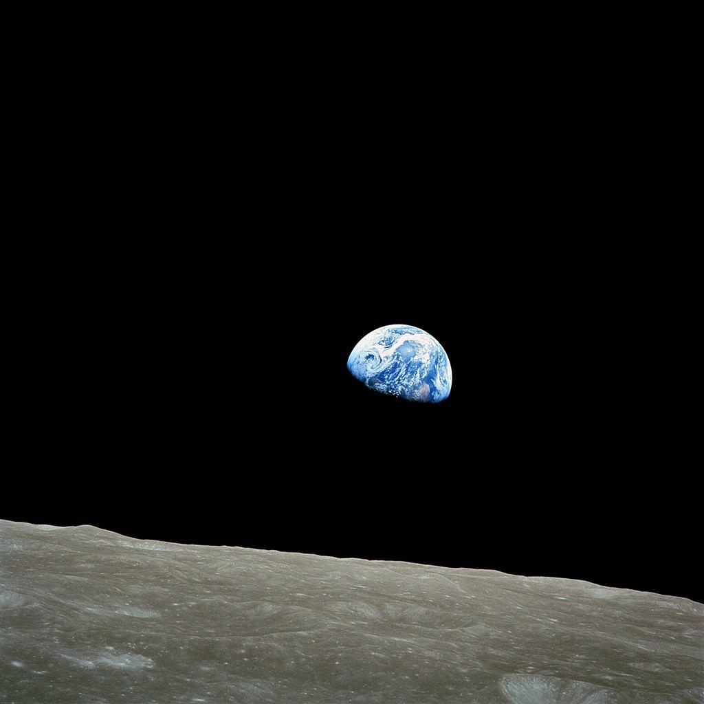 """""""Amanecer de la Tierra"""" desde la luna. Foto tomada el 24 de diciembre de 1968 por Bill Anders, que muestra la tierra que parece estar detrás del horizonte lunar. Este fenómeno es visible solo por alguien que orbita el astro. Debido a la rotación sincrónica de la luna, siempre se muestra la misma cara hacia la tierra, no vemos que la tierra se ve o se extiende desde la superficie de la luna."""