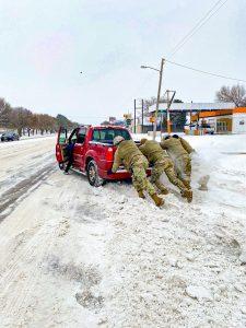 Inglés: Guardias de Texas ayudan a un automovilista atascado en la nieve y el hielo durante las condiciones meteorológicas invernales extremas en Abilene, Texas. Los miembros del Ejército de Texas, la Guardia Aérea y la Guardia Estatal trabajaron en apoyo del Departamento de Seguridad Pública de Texas y de la División de Gestión de Emergencias de Texas transportando personal a un lugar seguro, ayudando a los automovilistas varados, despejando las carreteras, atendiendo los centros de calentamiento, transportando al personal de infraestructura crítica al trabajo, y entregando productos básicos como agua, alimentos, mantas y oxígeno a los tejanos necesitados, del 12 al 20 de febrero de 2021. (Guardia Nacional del Ejército de Texas, cortesía de la sargento de personal Yvonne Ontiveros)